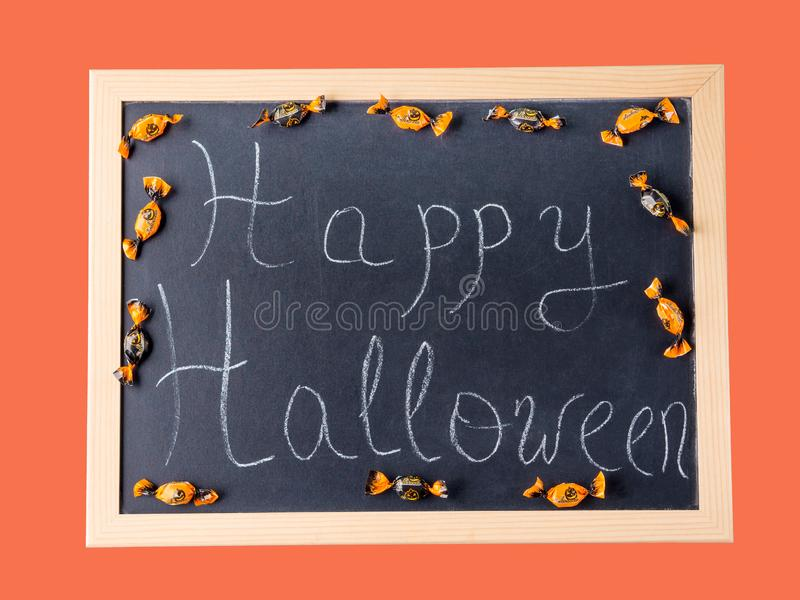 Happy Halloween. Holiday greetings on blackboard. Happy Halloween. Holiday greetings written with chalk on blackboard. Orange coral frame royalty free stock photo