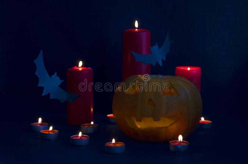 Happy Halloween holiday party Composition with Jack O` Lantern pumpkins, party decorations, bats and candles on blue background. royalty free stock image