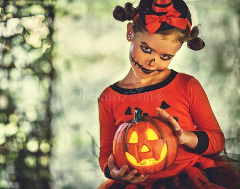 Happy Halloween! horrible creepy child girl in pumpkin costume royalty free stock photo