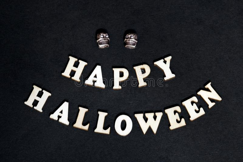Happy Halloween - inscription on a black background. Wooden words and two skulls for decoration on the day of all the saints. royalty free stock photos