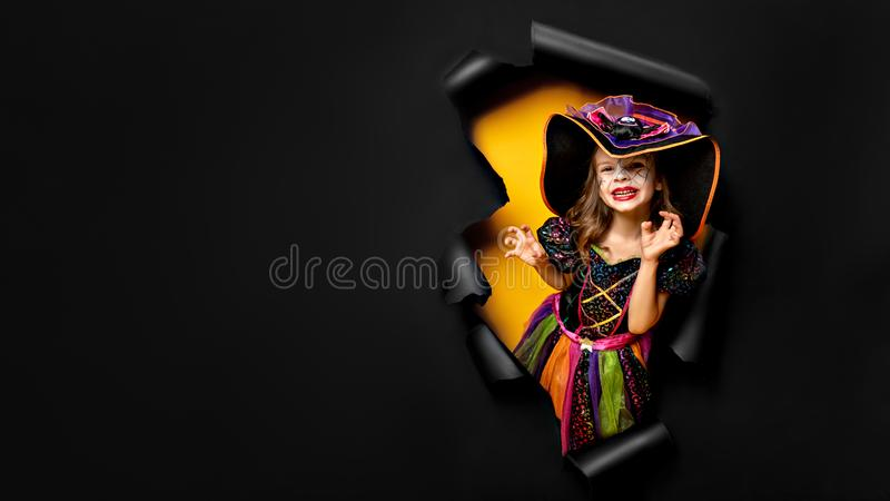 Laughing funny child girl in a witch costume in halloween stock photography