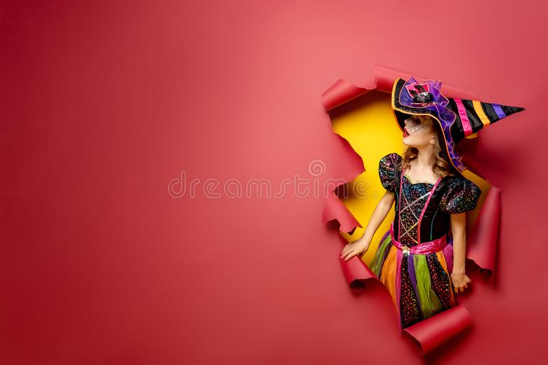 Laughing funny child girl in a witch costume in halloween stock photos