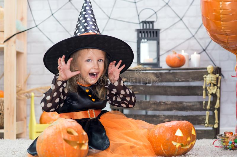 Happy Halloween. A little beautiful girl in a witch costume celebrates a home in an interior. With pumpkins stock images