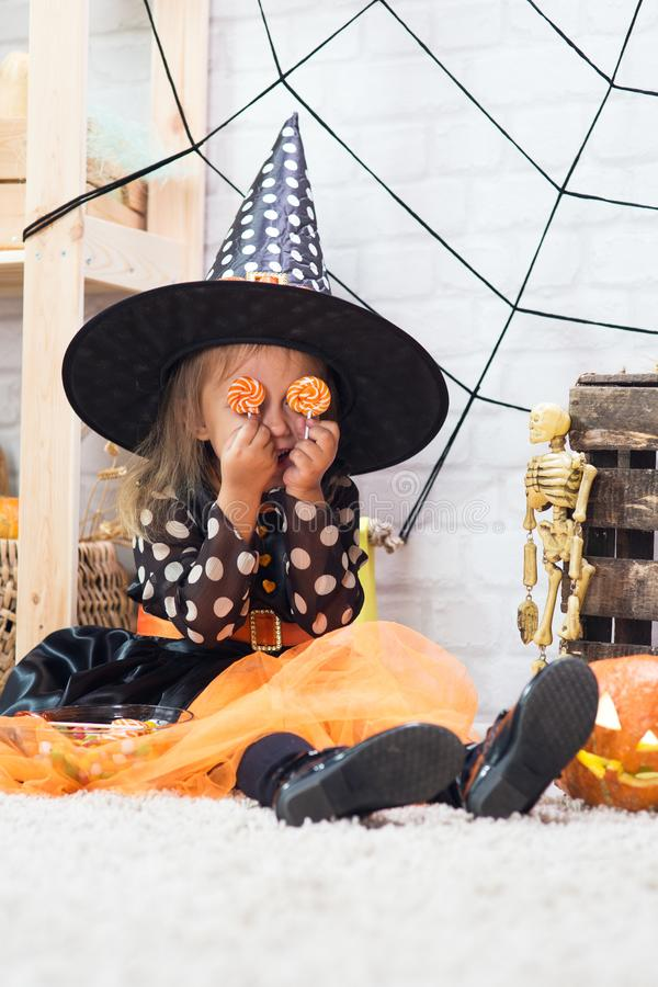 Happy Halloween. A little beautiful girl in a witch costume celebrates a home in an interior. With pumpkins royalty free stock images