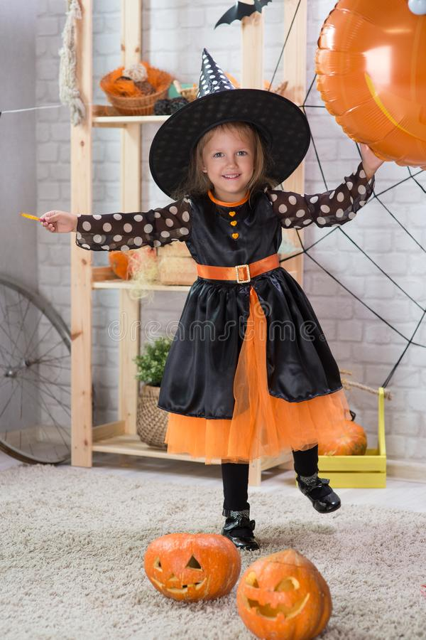 Happy Halloween. A little beautiful girl in a witch costume celebrates a home in an interior. With pumpkins royalty free stock image