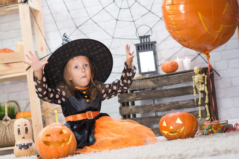 Happy Halloween. A little beautiful girl in a witch costume celebrates a home in an interior stock images