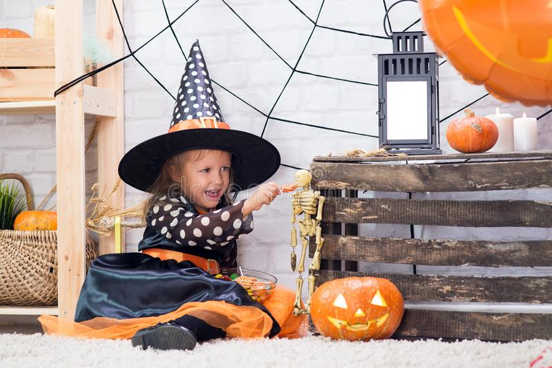 Happy Halloween. A little beautiful girl in a witch costume celebrates a home in an interior. With pumpkins stock image