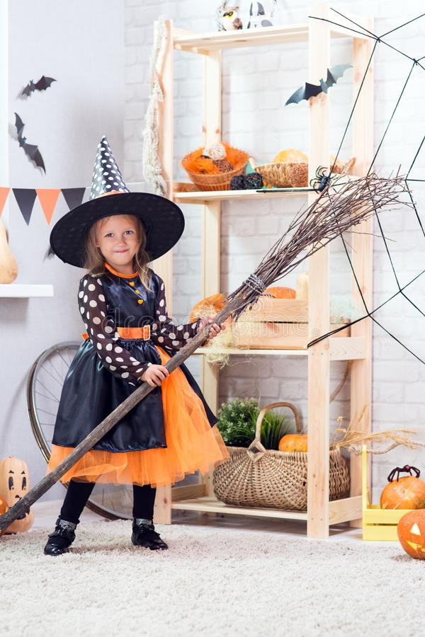 Happy Halloween. A little beautiful girl in a witch costume celebrates a home in an interior. With pumpkins stock photo