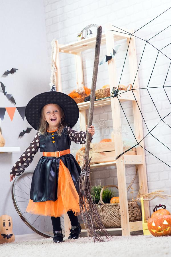 Happy Halloween. A little beautiful girl in a witch costume celebrates a home in an interior. With pumpkins royalty free stock photos