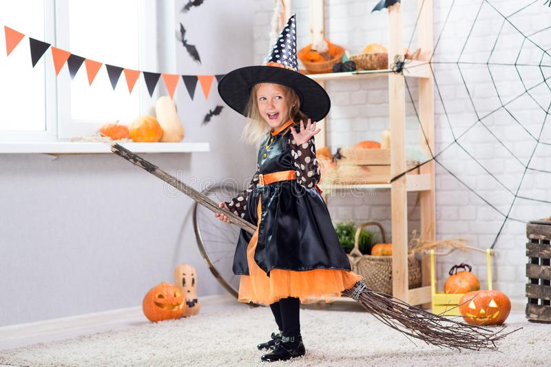 Happy Halloween. A little beautiful girl in a witch costume celebrates a home in an interior. With pumpkins royalty free stock photography