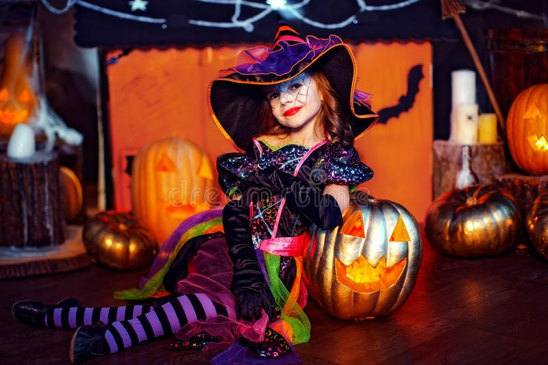 Happy Halloween. A little beautiful girl in a witch costume celebrates with pumpkins. Happy Halloween. A little beautiful girl in a witch costume celebrates at stock photography