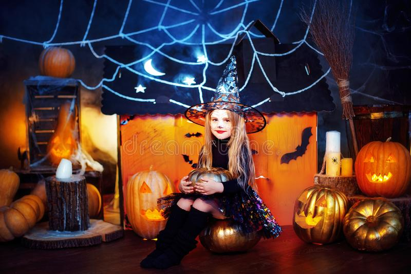 Happy Halloween. A little beautiful girl in a witch costume celebrates with pumpkins. Happy Halloween. A little beautiful girl in a witch costume celebrates at royalty free stock image