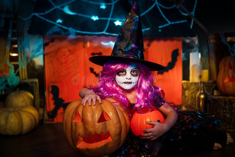 Happy Halloween. A little beautiful girl in a witch costume celebrates with pumpkins. Happy Halloween. A little beautiful girl in a witch costume celebrates at royalty free stock images