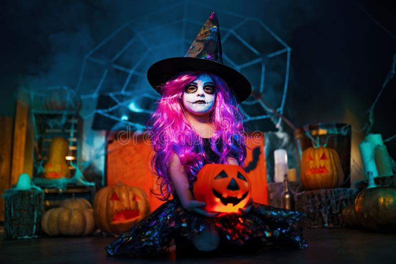 Happy Halloween. A little beautiful girl in a witch costume celebrates with pumpkins. Happy Halloween. A little beautiful girl in a witch costume celebrates at stock photo