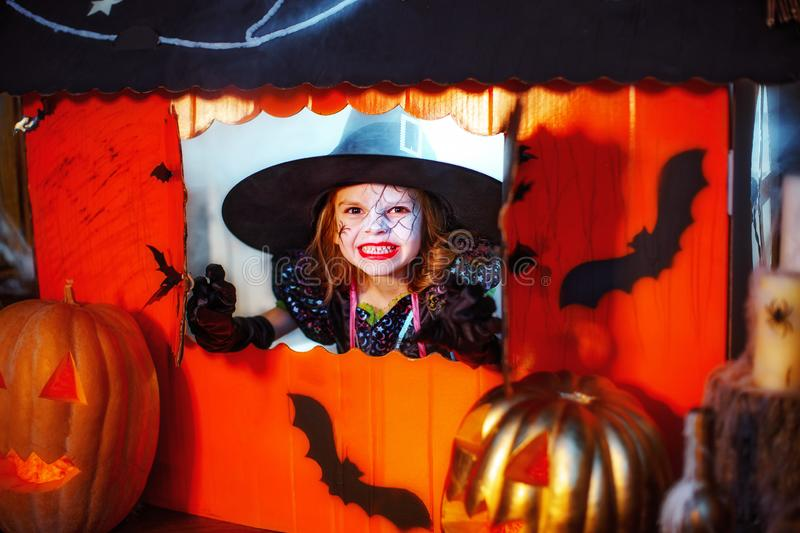 Happy Halloween. A little beautiful girl in a witch costume celebrates with pumpkins. Happy Halloween. A little beautiful girl in a witch costume celebrates at royalty free stock photography