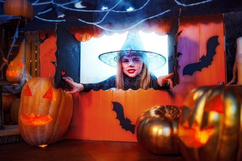 Happy Halloween. A little beautiful girl in a witch costume celebrates with pumpkins. Happy Halloween. A little beautiful girl in a witch costume celebrates at stock photos