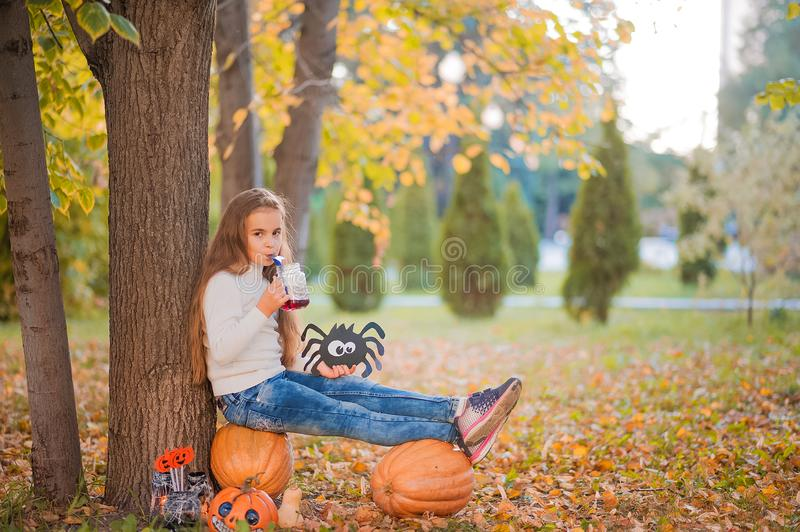 Happy Halloween! Little girl carving pumpkin at Halloween. Dressed up children trick or treating. Kids trick or treat. Toddler kid. With jack-o-lantern. Cute royalty free stock photos