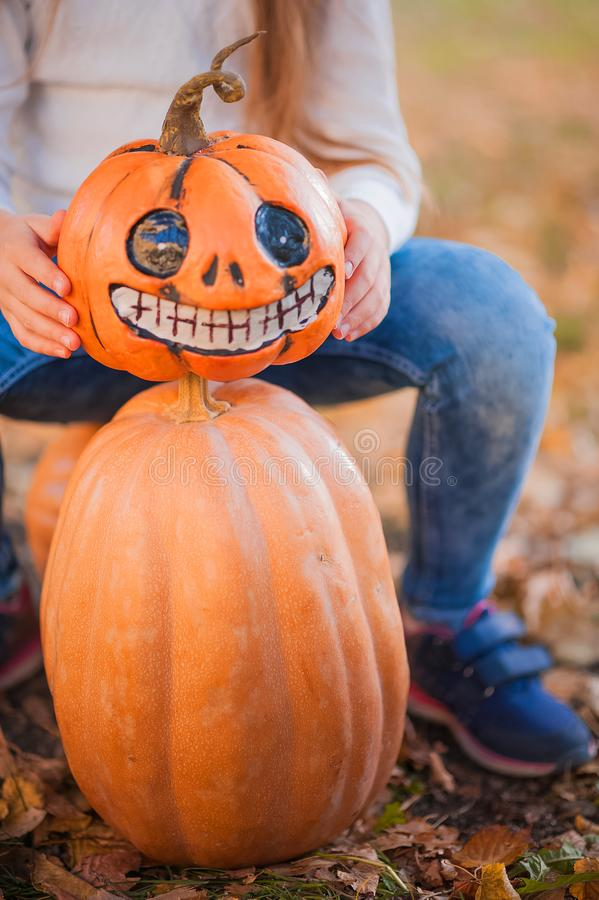 Happy Halloween! Little girl carving pumpkin at Halloween. Dressed up children trick or treating. Kids trick or treat. Toddler kid. With jack-o-lantern. Cute stock photos