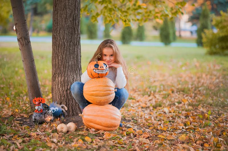 Happy Halloween! Little girl carving pumpkin at Halloween. Dressed up children trick or treating. Kids trick or treat. Toddler kid. With jack-o-lantern. Cute stock images