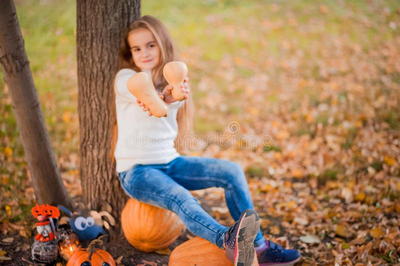 Happy Halloween! Little girl carving pumpkin at Halloween. Dressed up children trick or treating. Kids trick or treat. Toddler kid. With jack-o-lantern. Cute stock image