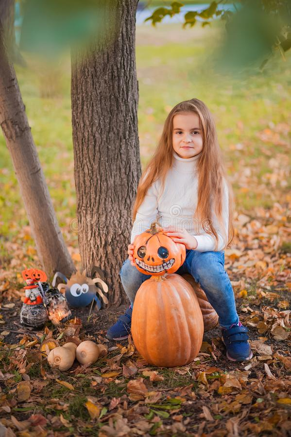 Happy Halloween! Little girl carving pumpkin at Halloween. Dressed up children trick or treating. Kids trick or treat. Toddler kid. With jack-o-lantern. Cute royalty free stock photography