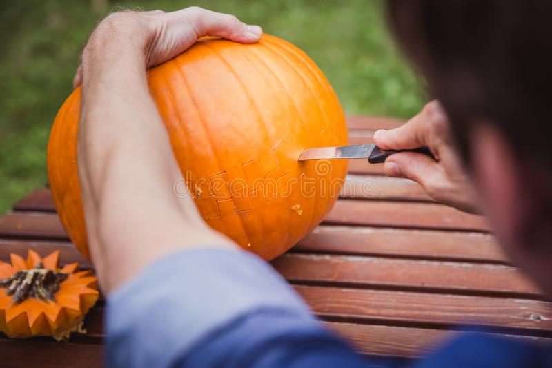 Happy halloween. Man carving big pumpkin Jack O Lanterns for Halloween outside. Close-up. Autumn royalty free stock image