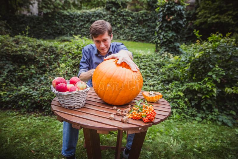 Happy halloween. Man carving big pumpkin Jack O Lanterns for Halloween outside. Close-up. Autumn stock photography