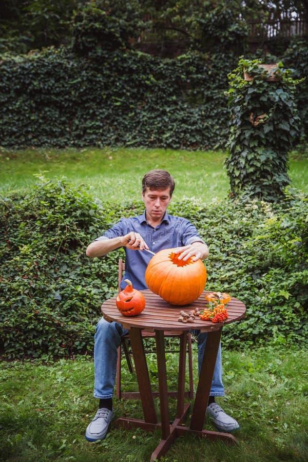 Happy halloween. Man carving big pumpkin Jack O Lanterns for Halloween outside. Close-up. Autumn stock image