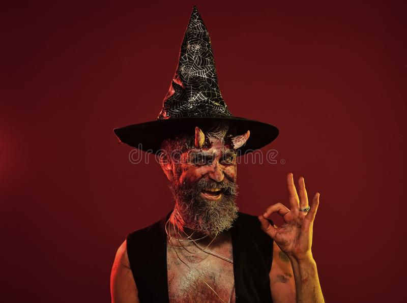 Happy Halloween man with devil horns in witch hat show ok. Satan hipster smile with beard, blood, wounds on red background. Hell, death, evil, horror concept stock photo
