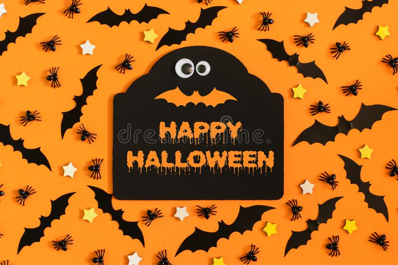 Happy Halloween. Many ornamental stars, little spiders and bats are lined with orange background. In the center there is. A figured tablet with an inscription royalty free stock images
