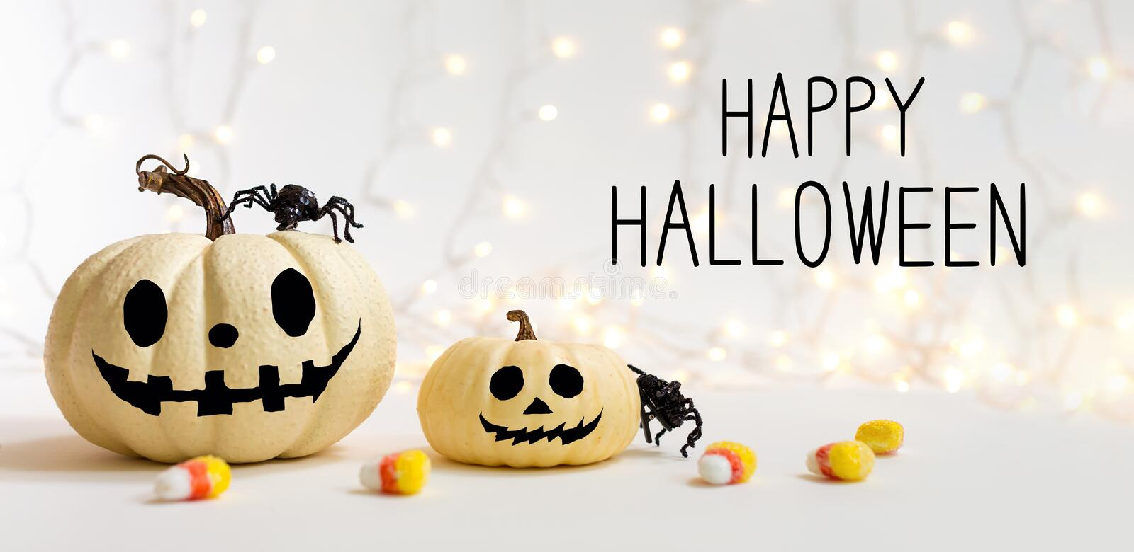 Happy Halloween message with pumpkins with spider. On a shiny light background stock photos