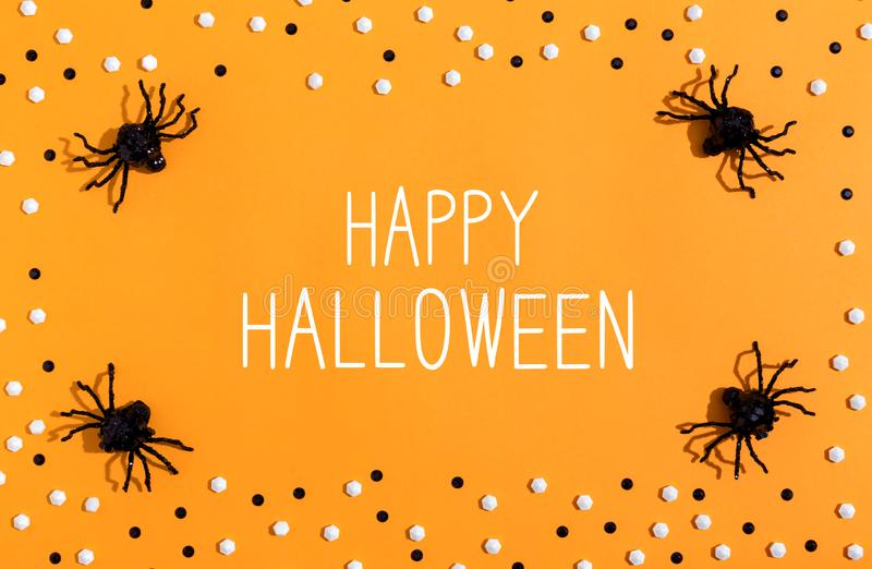 Happy Halloween message with spiders overhead view. On a solid color royalty free stock photos