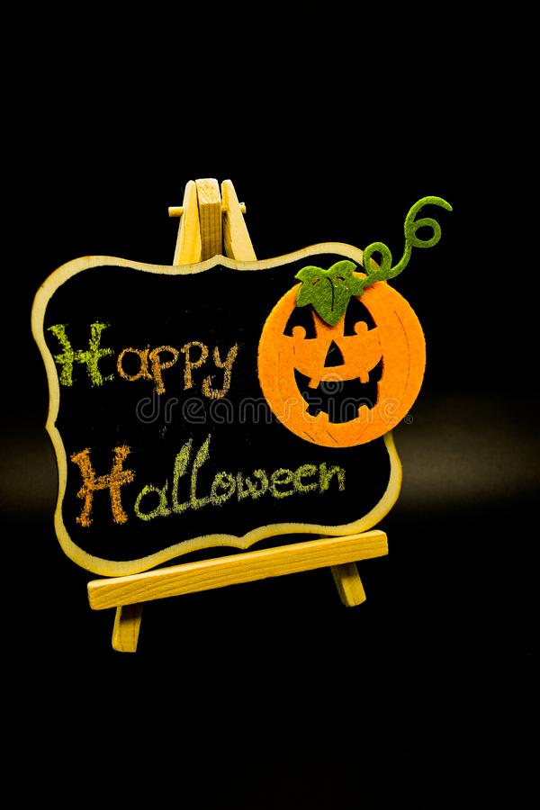 Happy Halloween message write on a blackboard with a pumpkin. Isolated on black background. Autumn orange pumpkin celebration. All Hallows` Even. Jack-o` royalty free stock photos