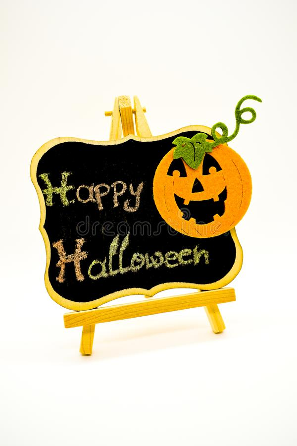 Happy Halloween message write on a blackboard with pumpkin. Isolated on white background. Autumn orange pumpkin celebration. All Hallows` Even. Jack-o`-Lantern royalty free stock photo