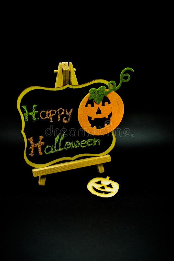 Happy Halloween message write on a blackboard with pumpkins. Isolated on black background. Autumn orange pumpkin celebration. All Hallows` Even. Jack-o` stock photography
