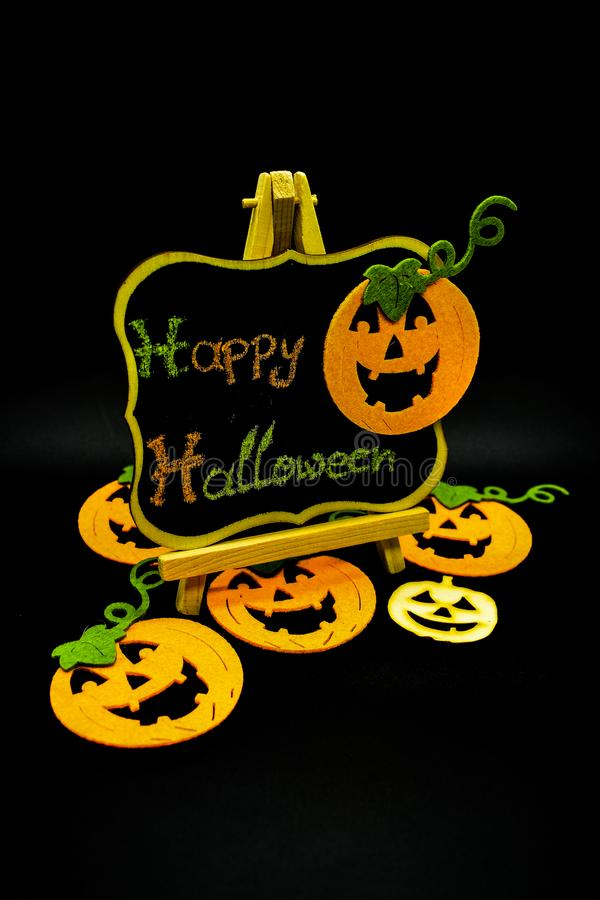 Happy Halloween message write on a blackboard with pumpkins. Isolated on black background. Autumn orange pumpkin celebration. All Hallows` Even. Jack-o` stock images
