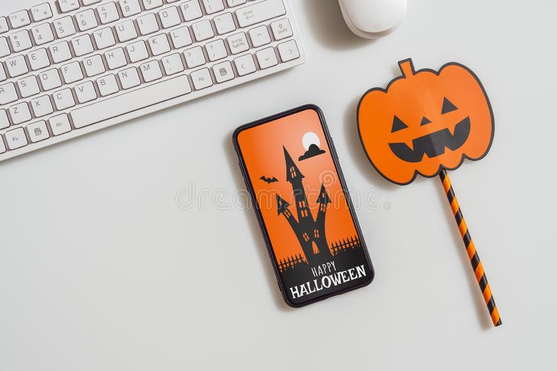 Happy Halloween Mobile phone mockup background concept. Top view of smartphone on office desk table with accessories. Flat lay. Design. Business and technology stock image