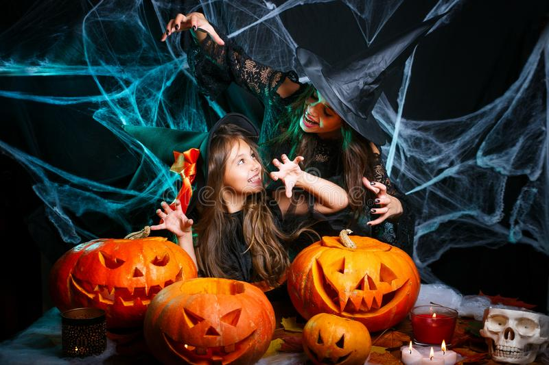 Happy Halloween. Mother and her daughter in witch costumes having fun at home. Mother and her daughter in witch costumes having fun at home. Happy Family royalty free stock image