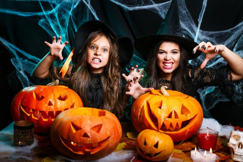 Happy Halloween. Mother and her daughter in witch costumes having fun at home. Mother and her daughter in witch costumes having fun at home. Happy Family royalty free stock photos