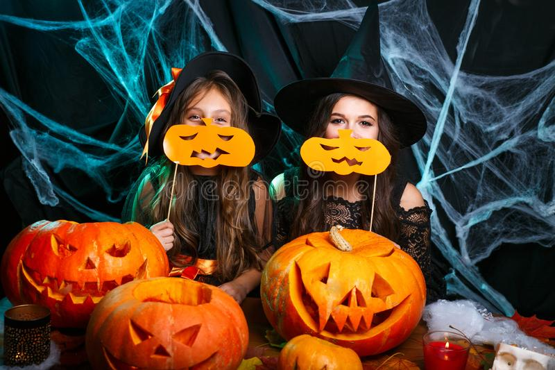 Happy Halloween. Mother and her daughter in witch costumes having fun at home. Mother and her daughter in witch costumes having fun at home. Happy Family royalty free stock photo