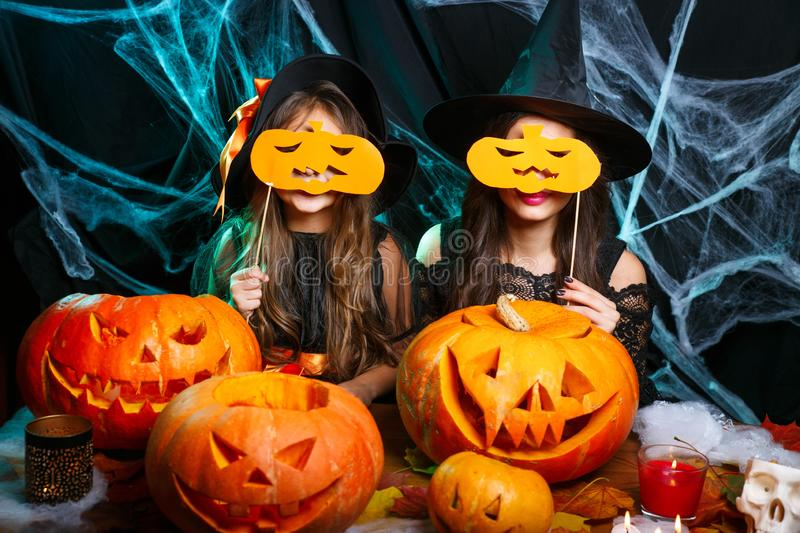Happy Halloween. Mother and her daughter in witch costumes having fun at home. Mother and her daughter in witch costumes having fun at home. Happy Family stock photography