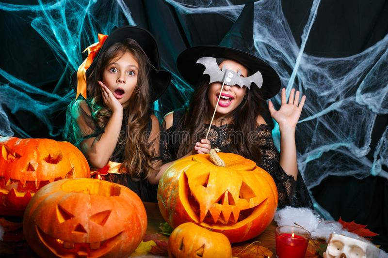 Happy Halloween. Mother and her daughter in witch costumes having fun at home. Mother and her daughter in witch costumes having fun at home. Happy Family stock photo
