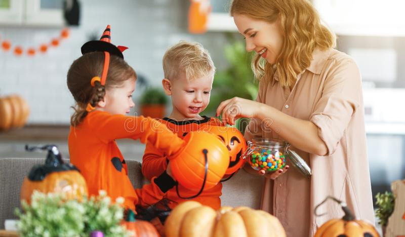 Happy Halloween! mother treats children with candy at home. Happy Halloween! a mother treats children with candy at home royalty free stock photos
