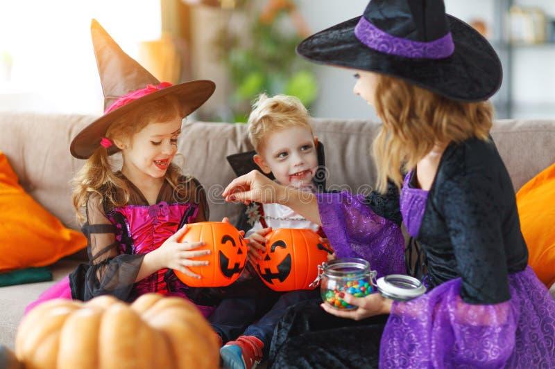 Happy Halloween! mother treats children with candy at home. Happy Halloween! a mother treats children with candy at home stock images