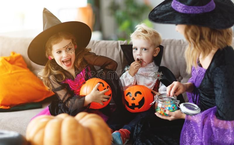 Happy Halloween! mother treats children with candy at home. Happy Halloween! a mother treats children with candy at home royalty free stock images