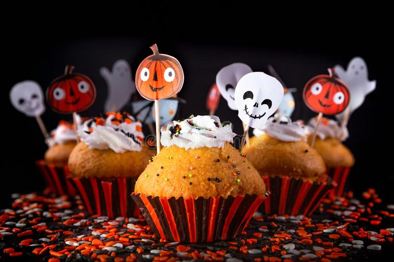 Happy Halloween muffin cupcakes. With funny party decorations set against a black background with differential focus and creative lighting royalty free stock photography