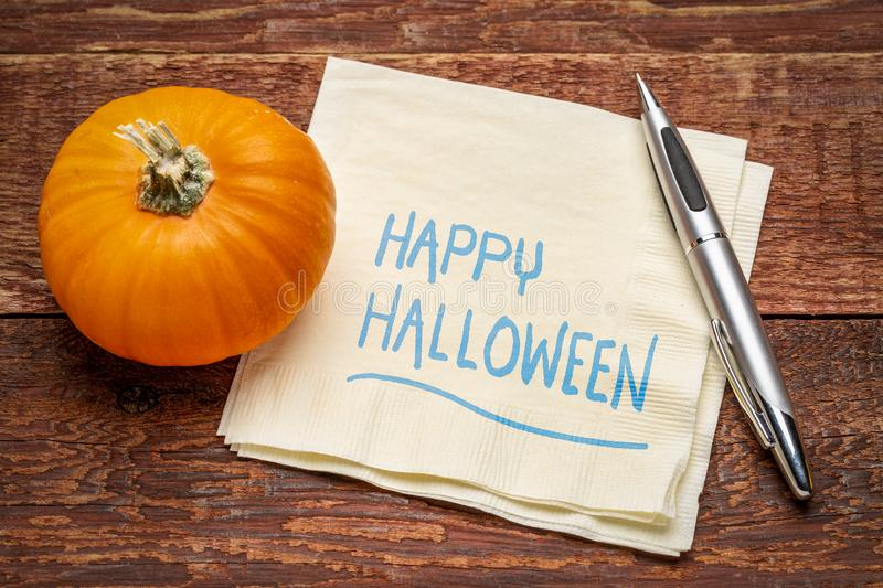 Happy Halloween on napkin. Happy Halloween greetings - handwriting on a napkin with a pumpkin gourd against rustic barn wood stock photos