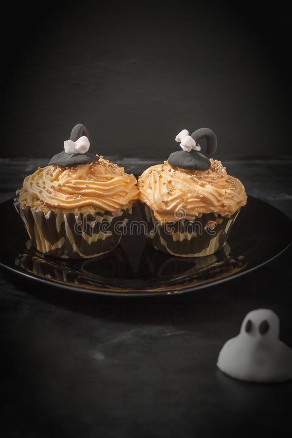 Happy Halloween orange and black decorated cupcake with a black witch hat and butter cream with beads on a black plate.  stock image