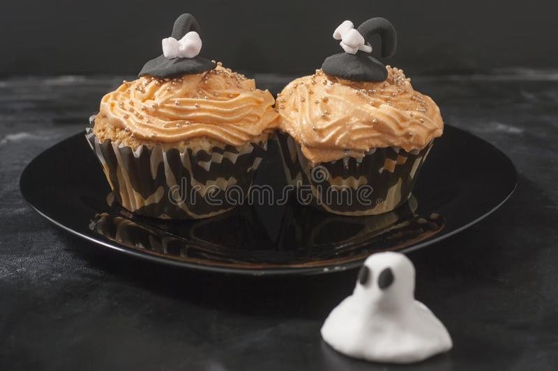 Happy Halloween orange and black decorated cupcake with a black witch hat and butter cream with beads on a black plate.  royalty free stock images