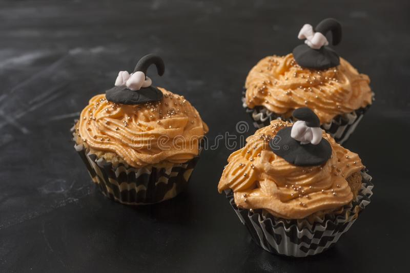 Happy Halloween orange and black decorated cupcake with a black witch hat and butter cream with beads. On a black background stock images